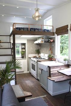 Tiny house interior with white walls, white appliances, farmhouse sink, wood bench, potted palm, lofted bed,wood floors, oriental rug, hanging light, and wood stairs.