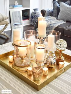 Make a visual statement with a clustered grouping of metal and glass candleholders in varying heights on your coffee table. Coffee Table Tray, Coffee Table Styling, Decorating Coffee Tables, Tray Decor, Decoration Table, Centerpiece Ideas, Dining Room Table Centerpieces, Ottoman Decor, Candle Tray
