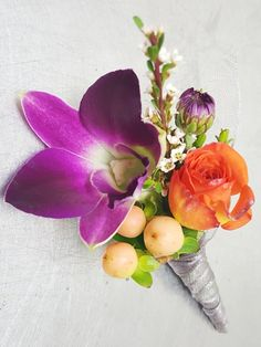 Purple orchid magnetic groom's boutonniere with orange spray rose, peach hypericum and purple mum bud from Seasonal Celebrations.