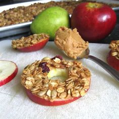 Granola Apple Rings sliced apples spread with peanut butter dipped in granola--a healthy, delicious dessert! This would taste great baked, or even nuked. Lunch Snacks, Yummy Snacks, Delicious Desserts, Snack Recipes, Yummy Food, Healthy Recipes, Celiac Recipes, Kid Recipes, Easy Snacks