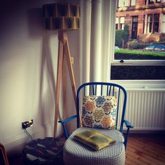 Ercol chair with Orla Kiely cushion and lampshade. Habitat oak light stand. Lucienne Day pouffe by Heals.