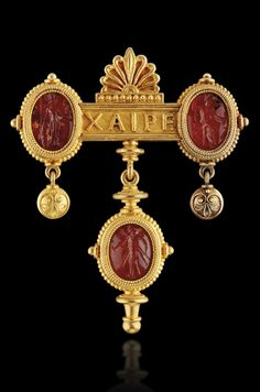CASTELLANI - AN ARCHAEOLOGICAL REVIVAL GOLD AND CARNELIAN BROOCH, CIRCA 1850. The bar inscribed XAIRE (hallo) with a palmette surmount flanked by two carnelian intaglios, one depicting Minerva, the other depicting Jupiter, each within an oval mount with rope-twist and small beads suspending two small pendants, with another carnelian intaglio pendant below, depicting a warrior. Castellani's monogram on verso.