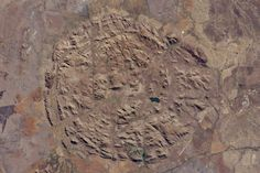Concentric circles of rocky hills and valleys in South Africa tell a story of a billion-year-old collapsed volcano in newly released photos from NASA.