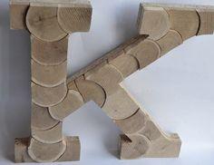 Duża litera 3D, wykonana z płyty oraz krążków dębowych.