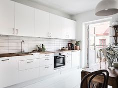 Solo con ver las puertas de esta casa podrás imaginarte que todo lo que hay en su interior es especial. Una vivienda con suelos blancos donde la madera tiene gran protagonismo.