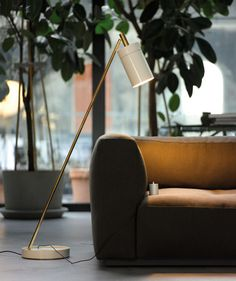 Design Carsten Gollnick.  Anta Nobu floor lamp. Tilting floor lamp with reflector and lamp base in high-polish pearl-white varnish, metal parts in slightly darkened brass. Detachable corded on/off switch...