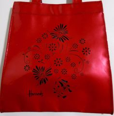 "Harrods red metallic vinyl tote bag with a cut out flower design. Measures 12"" x 10 1/2"" x 4 1/2"", strap drop of 5"". Good condition, clean inside and out. 