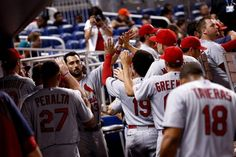 MIAMI, FL - AUGUST 11: Matt Carpenter #13 of the St. Louis Cardinals high-fives teammates after scoring during the ninth inning of the game ...