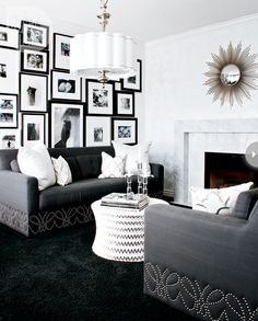 Hollywood drama /   Black-and-white has never looked so decadent. Inspired by a tuxedo, this living room seduced us with its old Hollywood glamour from the crisp white walls to the luxe black carpet to the glitzy nailhead details and lighting fixture.