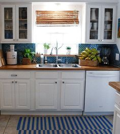 butcher block counter tops in blue and white kitchen | white cabinets, blue backsplash, butcher block counters
