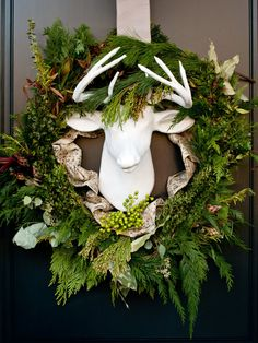 This festive front door starts with a faux reindeer head surrounded by green leaves and branches. The holiday front door wreath leans more modern than rustic with an all-white paint job on the head. Best Outdoor Christmas Decorations, Diy Christmas Lights, Christmas Greenery, Farmhouse Christmas Decor, Christmas Cards To Make, Xmas Decorations, Christmas Ideas, Christmas Planters, Outdoor Decorations