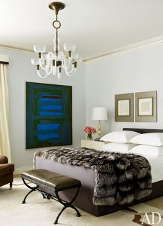 In a Delphine Krakoff-designed bedroom, the bed is dressed in monogrammed sheets and a fur throw.