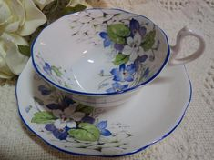 Absolutely Charming! Made by Royal Albert, Crown Bone China, England. Gorgeous white and purple floral spray over white background and trimmed with purple.........Both pieces are in lovingly used condition with no chips, cracks, crackling or repairs. Measurements: Saucer 5.5,