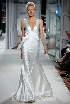 Brides.com: Pnina Tornai for Kleinfeld - 2014. Style 4279, silk charmeuse sheath wedding dress with plunging neckline and criss-cross back with bow detail, Pnina Tornai for Kleinfeld