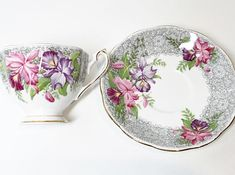 Large beautiful orchids caress the curves of this classic Queen Anne Fine Bone China tea cup and saucer. This antique English bone china teacup and saucer is called Nottingham Lace. Queen Anne teacups are noted for their taller, paneled design. They were produced by the Shore and