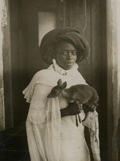 kilele:    A stylish young Kenyan woman holding her pet deer in Mombasa, Kenya (1909)