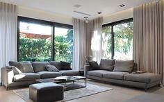 graue Sofas, rechteckiger Glas Couchtisch und heller Laminatboden