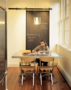 suspended blackboard hides the water heater   Dwell