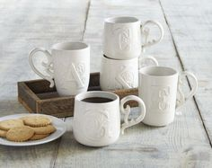 Stoneware mugs with raised flourished initial and sculpted handles, $12 each