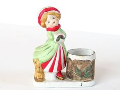 Darling little girl skater with her pet bunny stands next to a Christmas votive candleholder (candle not included) painted like a tree stump