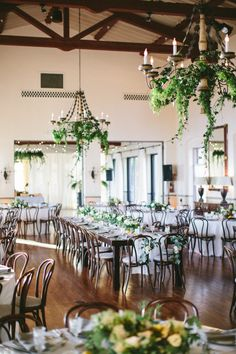 chandeliers accented with greenery | bentwood dining chairs | wooden harvest tables | long banquet style dining tables | indoor wedding reception | Bel-Air Ballroom Wedding with Shades of Green