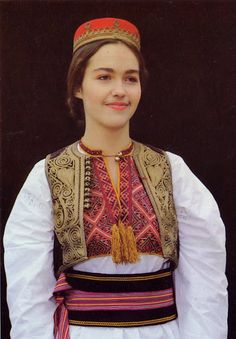 Costume of South Dubrovnik County, Konavlje, Čilipi, Dalmatia, Croatia- A wide, very stiff sash is wrapped around the waist over the apron and  chemise. This is so stiff that it cannot be tied or tucked in. A narrow silk ribbon is therefore tied over the sash to hold it in place.