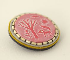 Embossed pin  by Elsa Mora - paper cut embossed onto polymer clay....would be great for water etching project