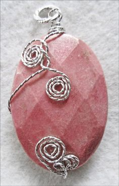 Rhodonite & Sterling Silver Twist Pendant by MoonbeamsLilacsRoses -- Miriam uses only natural stones, and this bold, beautifully faceted oval pendant shows all the natural color, texture and beauty of natural Rhodonite. Miriam's Signature Sterling Silver Twists add a unique statement to this outstanding stone.   The Rhodonite stone measures 2 inches long, 1.5 inches wide at its center, and is 0.25 inches thick. The Pendant plus Sterling Silver bale measures 2.5 inches. Priced at $160.