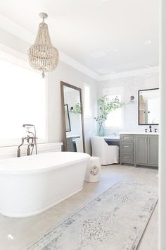 An oval, freestanding bathtub with a oil rubbed bronze vintage filler, sits amidst an open concept bathroom design.