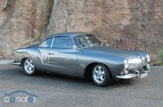 1960 Karmann Ghia. Mine was a 1960, but it had the bumpers shaved, nose filled, lowered a few inches and Porsche rims and hubcaps.