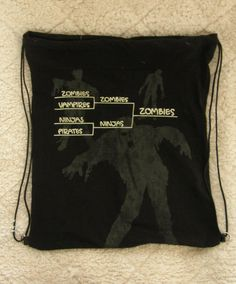 Handmade by me, up-cycled vintage t-shirt draw string back pack.  Zombies, vampires,ninjas and pirates t-shirt that has been up cycled and lined. and sewn into a draw string back pack.    READY TO SHIP today.  T-shirts are hand picked, washed, and up-cycled into a unique draw string back pack.  They are lined for durability, parachute cord for the draw string closure and double sewn seams.  Measures 16 wide and 18 1/2  tall.  Washable and dry able on low heat, durable and strong.  Any q...