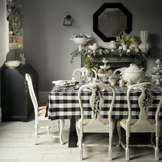 Black and white hues combine to create a contemporary Scandinavian look in this sophisticated dining room, as do the oversized check tablecloth, antique chairs and painted furniture. Chic silver and white decorations with touches of foliage add a healthy dollop of festive charm.