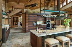 "Colorado home-""Everything in the house wraps around the kitchen area,"" says Grace, who chose a leathered granite for the top of the island and cabinets made of richly colored fumed larch. ""I purposely made the kitchen very casual—I wanted to be able to put out tons of food, buffet style, and let people mingle."""