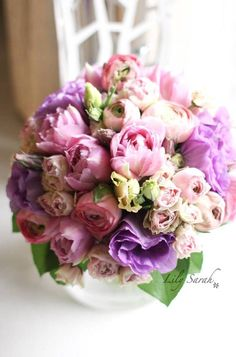 a charming bouquet of pretty tulips, eustoma, ranunculus and mini roses.