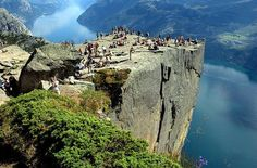 """Preikestolen, Norway --- Preikestolen or Prekestolen, also known by the English translations of Preacher's Pulpit or Pulpit Rock, and by the old local name Hyvlatonnå (""""the carpenter-plane's blade""""), is a massive cliff 604 metres (1982 feet) above Lysefjorden, opposite the Kjerag plateau, in Forsand, Ryfylke, Norway. The top of the cliff is approximately 25x25 metres (82x82 feet) square, almost flat, and is a famous tourist attraction in Norway."""