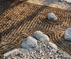 Raked gravel surrounding stones represents ripples of waves around islands. This type of Zen or Japanese garden is designed for contemplative thought and is super-easy to maintain./