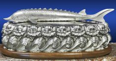 "A large silver caviar server. Hallmarked ""London 2002"". Fitted with five glass dishes in a framework and a liner for crushed ice. 90 cm long, 53 cm wide, 35 cm tall. Photo courtesy Galerie de Bartha"