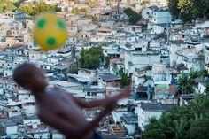A Brazilian boy playing football amid the backdrop of Sao Carlos favela in Rio de Janeiro