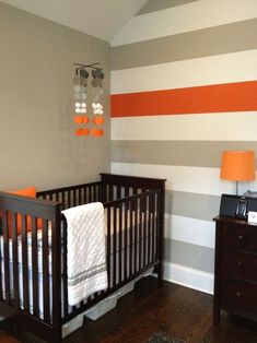 nursery accent wall // coral or teal stripe instead of orange // love the pop of color from the lamp shade too //