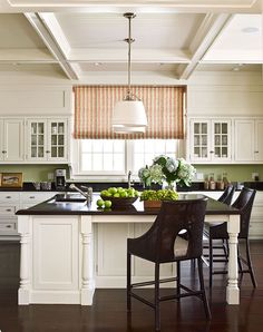 A boxed beam ceiling with beadboard insets and simple cabinets with chrome hardware give the kitchen a vintage feel. A Roman shade in Bijou Stripe from China Seas adds a pop of warm color, and caned-back bar stools from Thomas Pheasant for McGuire offer comfortable seating at the island.