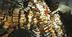 An assistant imam checks books taken to a mosque for safekeeping after reportedly being looted from Iraq's national library after the fall o...