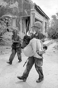 """10 Sep 1965, Qui Nhon, South Vietnam -- While most of the men in a village, north of Qui Nhon, fled their homes as the US Marines marched in, some still remained. Here, Cpl. John Glover of Miami, FL, carries a sick old Vietnamese man to an aid station as a Marine buddy walks nearby looking for snipers, the """"unknown enemy"""", that constantly threatens the leathernecks in a village which was heavily infiltrated by the Viet Cong."""