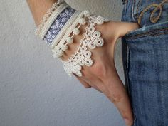 beaded crochet bracelet with white and blue-gray embroidered base and white seed bead decorations by irregularexpressions