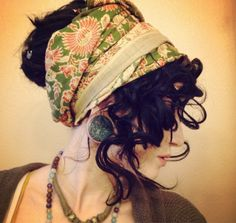 Tight curls, secured bun, loose bangs, and a tied scarf