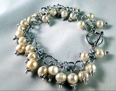 """Freshwater Pearls with pewter accents dangle from a handcrafted orbital aluminum chain. It's finished with a pewter toggle clasp. 7 1/2"""" in length. 55.00"""