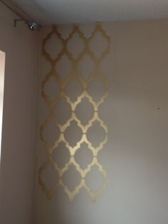 Tutorial on how you can create a geometric print wall in your own home using spray paint and a stencil.