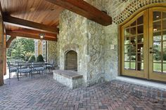 Large covered patio with vaulted wood ceiling.  Patio material is brick with large stone fireplace.