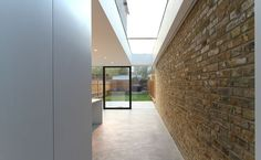Side return extension - Like the height, the brick feature wall, the flat glass roof. Looks like there is some lighting in the top strip where the brick wall joins the white roof - would make a good feature in the dark as well as light.