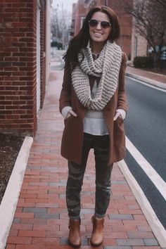 Sydney looks cozy in these camo pants, chunky sweater and scarf and brown coat (from The Daybook)
