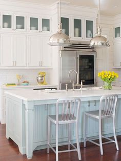 Contemporary kitchen with bright white walls and cabinets, silver kitchen stools & glass front cabinets